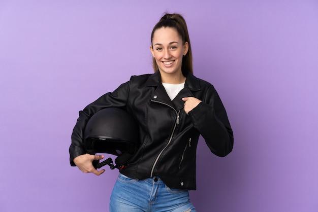 驚きの表情で孤立した紫色の壁の上のオートバイのヘルメットを持つ若いブルネットの女性