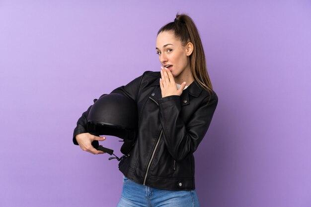 驚きとショックを受けた表情で分離された紫色の壁の上のオートバイのヘルメットを持つ若いブルネットの女性