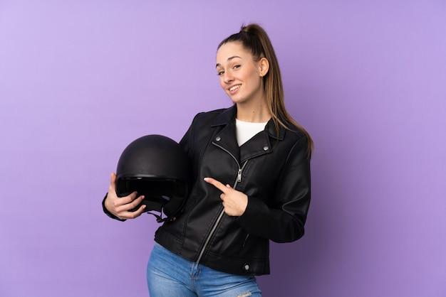 孤立した紫色の壁の上のオートバイのヘルメットとそれを指している若いブルネットの女性