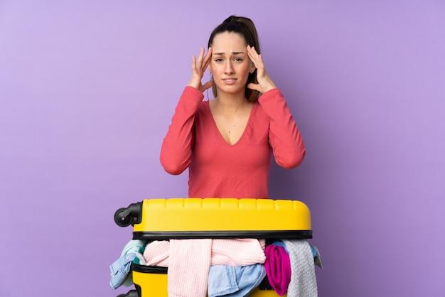 不満と何かに不満の孤立した紫色の壁の上の服でいっぱいのスーツケースを持つ旅行者の女性。負の表情