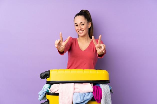 Путешественник женщина с чемоданом, полным одежды над изолированных фиолетовый стены, улыбаясь и показывая знак победы