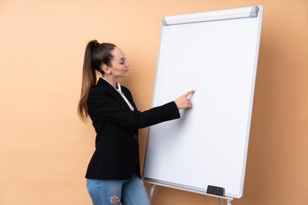 Молодая бизнес-леди над изолированной стеной давая представление на белой доске и писать в нем