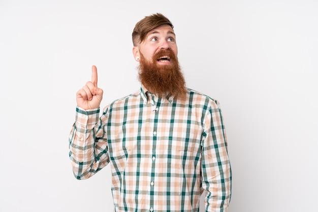 Рыжий мужчина с длинной бородой на белом фоне, указывая вверх и удивлен