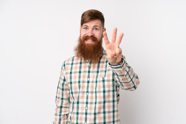 Рыжий мужчина с длинной бородой над изолированной белой стеной счастлив и считает три пальца