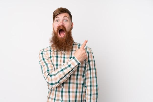 Рыжий мужчина с длинной бородой на изолированной белой стене удивлен и указывая сторону