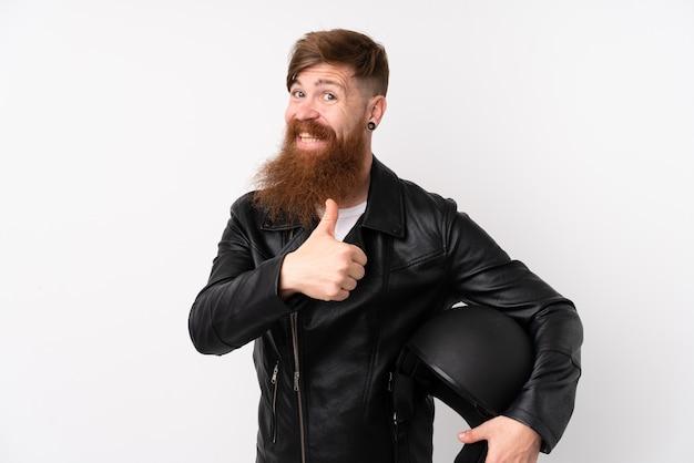 Рыжий мужчина с длинной бородой держит мотоциклетный шлем над изолированной белой стеной, давая недурно жест