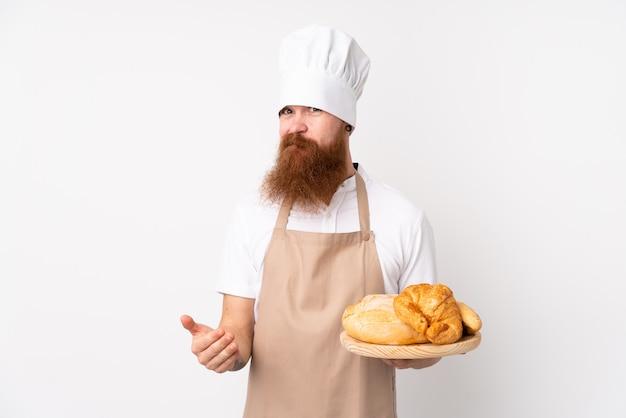 シェフの制服を着た赤毛の男。肩を持ち上げながら疑わしいジェスチャーを作るいくつかのパンとテーブルを保持している男性のパン屋