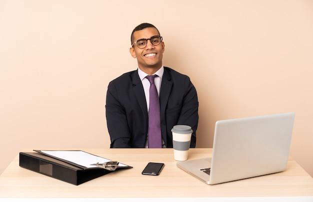 Молодой деловой человек в своем офисе с ноутбуком и другими документами смеяться