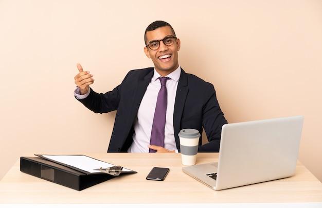 Молодой деловой человек в своем офисе с ноутбуком и другими документами, делая жест гитары