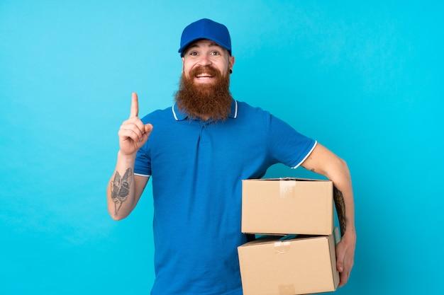 Рыжий доставщик по синей стене, указывающей отличная идея