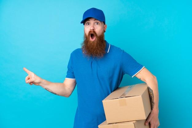 Рыжий доставщик над синей стеной удивлен и указывая сторону