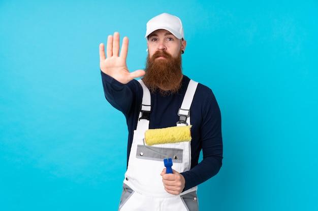 彼女の手で停止ジェスチャーを作る分離の青い壁の上の長いひげを持つ画家男