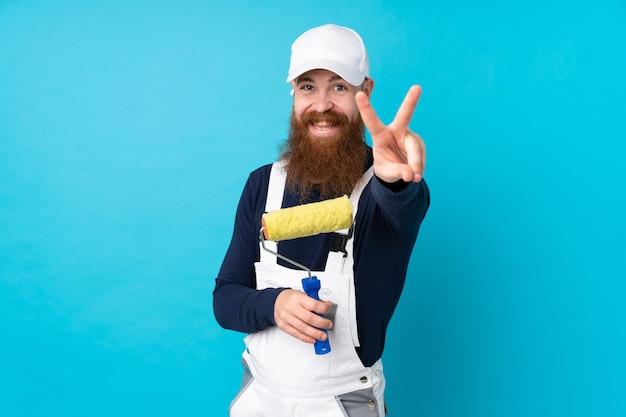 笑みを浮かべて、勝利のサインを示す分離の青い壁の上の長いひげを持つ画家男