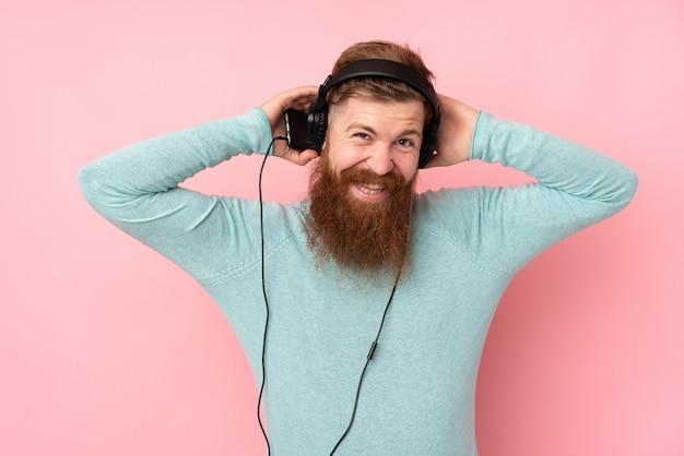 音楽を聴く分離ピンクの壁の上の長いひげを持つ赤毛の男