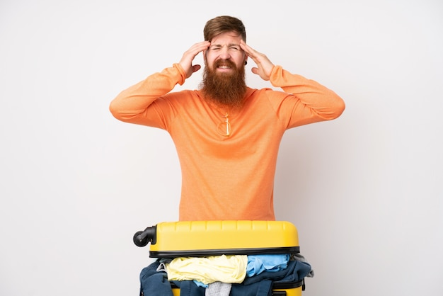 不幸で何かに不満の孤立した白い壁の上の服の完全なスーツケースを持つ旅行者男。負の表情