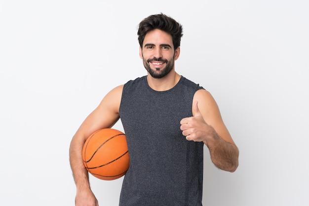 Молодой красавец с бородой на изолированной белой стене, играл в баскетбол и с пальца вверх