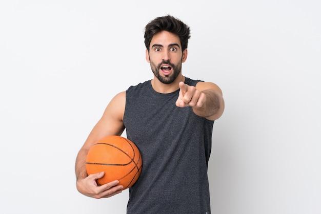 Баскетболист человек с бородой на изолированной белой стене удивлен и указывая вперед