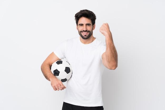 Молодой красивый человек с бородой над изолированной белой стеной празднует победу