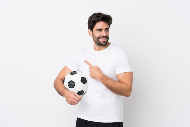 Молодой красавец с бородой над изолированной белой стеной, указывая в сторону, чтобы представить продукт