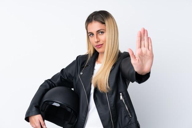 彼女の手で停止ジェスチャーを作る分離の白い壁の上のオートバイのヘルメットを持つ若い女性
