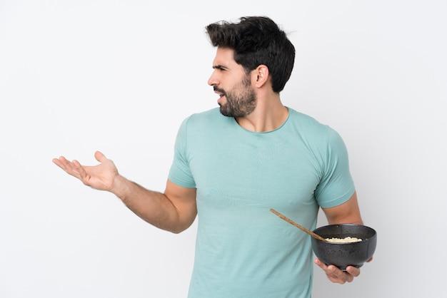 箸で麺のボウルを押しながら驚きの表情で孤立した白い壁の上のひげを持つ若いハンサムな男
