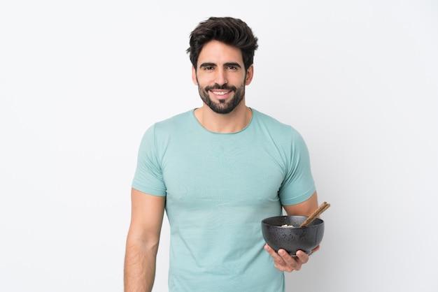 箸で麺のボウルを押しながら笑みを浮かべて孤立した白い壁の上のひげを持つ若いハンサムな男