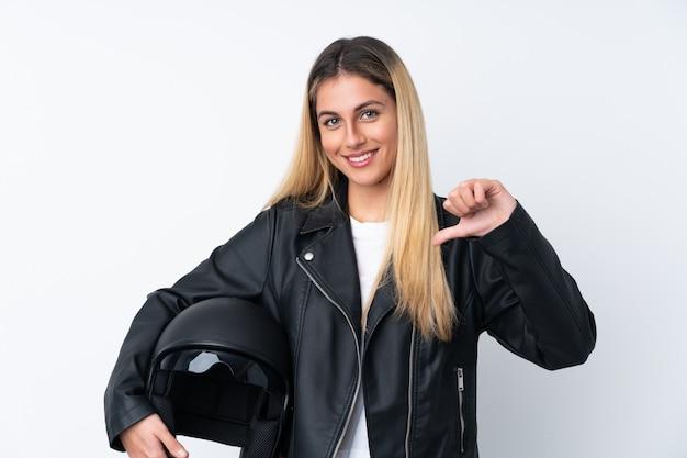 誇りと自己満足の分離の白い壁の上のオートバイのヘルメットを持つ若い女性