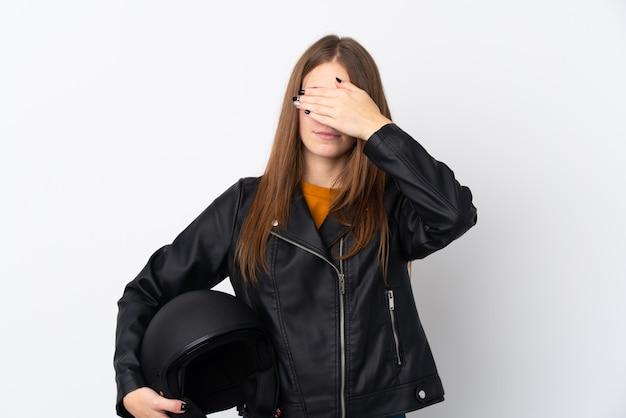 手で目を覆っているオートバイのヘルメットを持つ女性