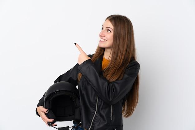 人差し指で素晴らしいアイデアを指しているオートバイのヘルメットを持つ女性