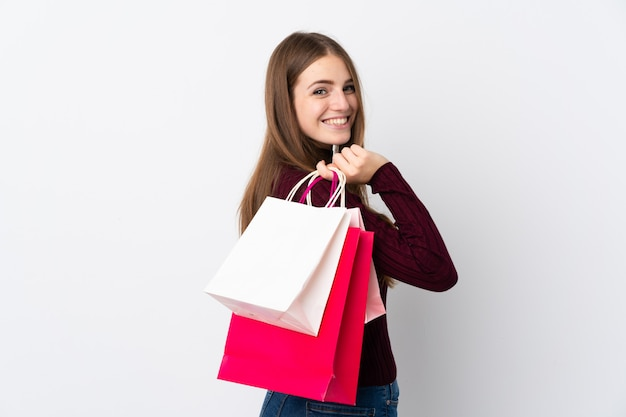 買い物袋を押しながら笑みを浮かべて分離の白い壁の上の若い女性