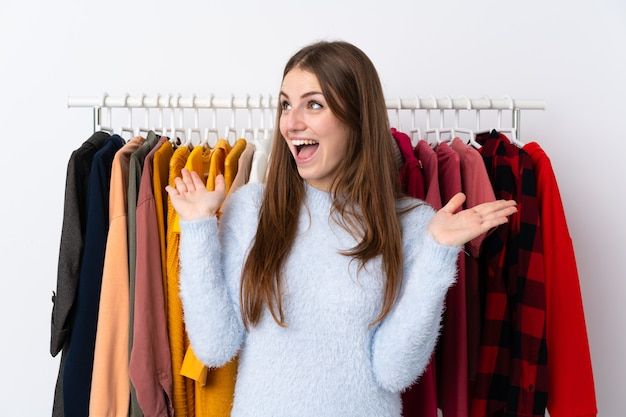 Молодая женщина в магазине одежды с удивленным выражением лица