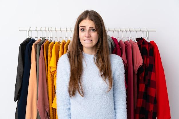 Молодая женщина в магазине одежды, имеющие сомнения и с выражением лица путать