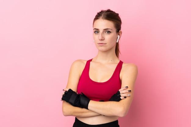 腕を組んで保つ分離のピンクの壁の上の若いスポーツ女性