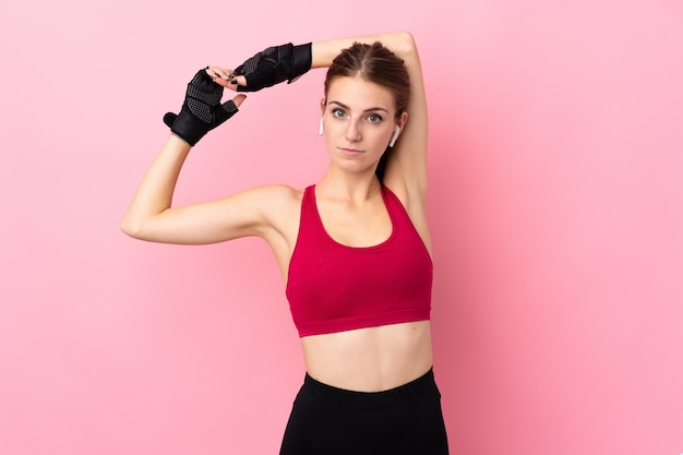 孤立したピンクの壁のストレッチ上の若いスポーツ女性