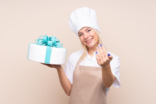 手で来ることを招待して孤立した壁の上の大きなケーキを持つ若い女性。あなたが来て幸せ