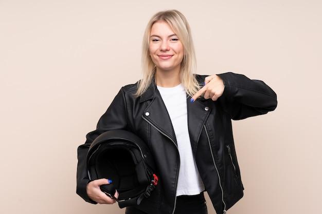 孤立した壁の上のオートバイのヘルメットとそれを指している若いブロンドの女性