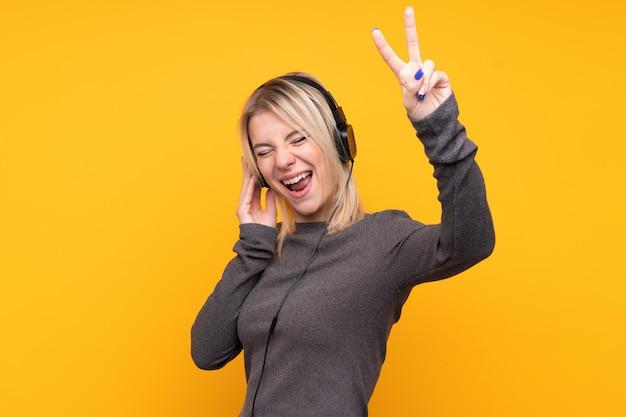 Молодая белокурая женщина над изолированной музыкой желтой стены слушая и петь