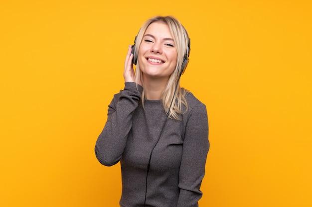 Молодая белокурая женщина над изолированной музыкой желтой стены слушая