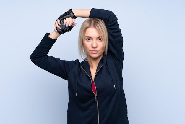 孤立した青い壁のストレッチ上の若いスポーツブロンドの女性