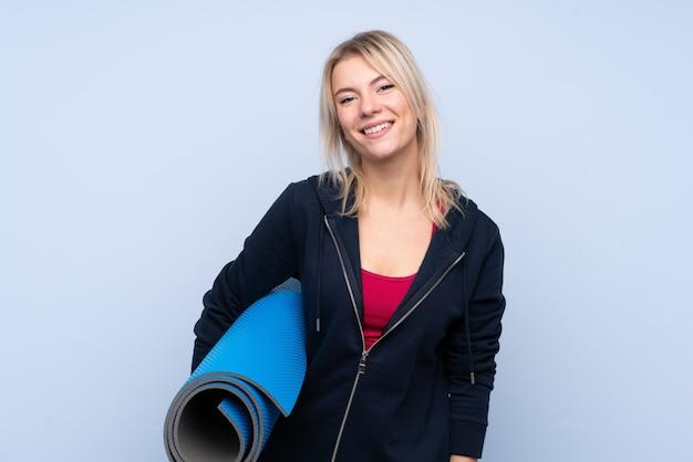 Молодая спортивная блондинка над изолированной синей стеной с циновкой и улыбкой