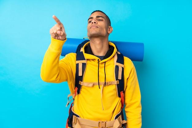 透明な画面に触れる分離の青い壁の上の大きなバックパックを持つ若い登山家男