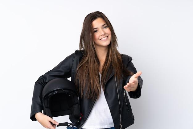 かなりの後に孤立した白い壁のハンドシェーク上のオートバイのヘルメットを持つ若い女性