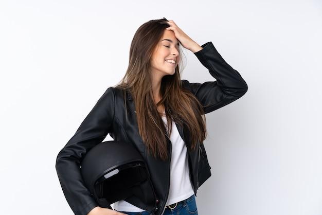 孤立した白い壁の笑いの上のオートバイのヘルメットを持つ若い女性