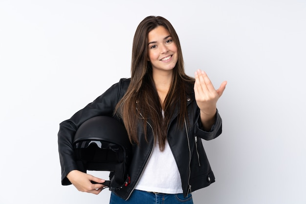 来ることを招待して孤立した白い壁の上のオートバイのヘルメットを持つ若い女性