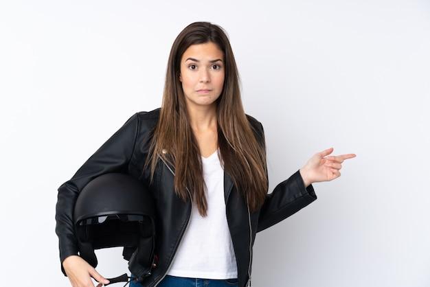 疑問を持っている側面を指している分離の白い壁の上のオートバイのヘルメットを持つ若い女性