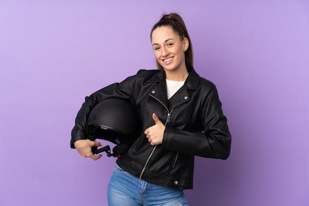 何か良いことが起こったので親指で孤立した紫色の壁にオートバイのヘルメットを持つ若いブルネットの女性