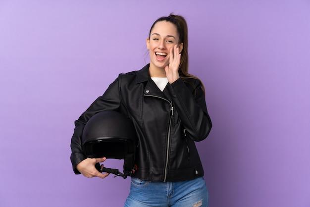 口を大きく開けて叫んで分離の紫色の壁の上のオートバイのヘルメットを持つ若いブルネットの女性