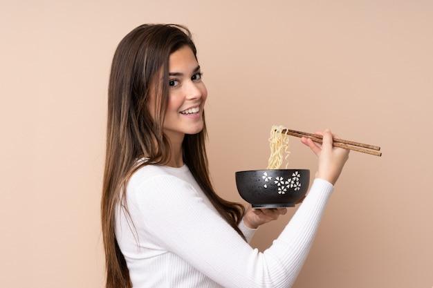 Девушка-подросток над изолированной стеной держит миску лапши с палочками для еды