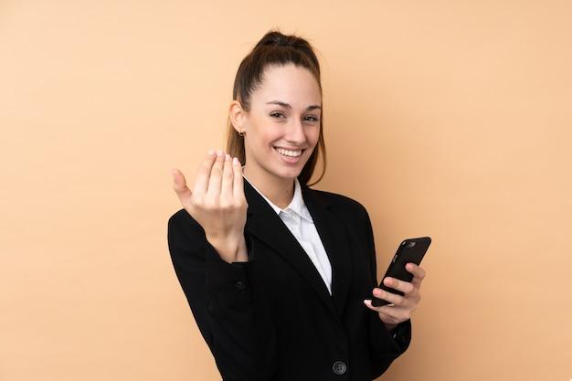 若いビジネス女性の手に来るように招待分離壁を越えて携帯電話を使用して。あなたが来て幸せ