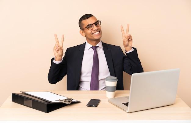 Молодой деловой человек в своем офисе с ноутбуком и другими документами, показывающими знак победы обеими руками